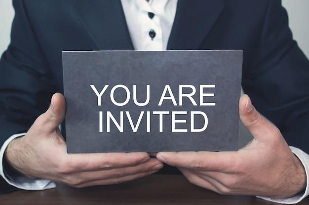 Homme d'affaires montrant le texte vous êtes invité.