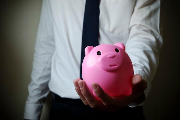 Homme d'affaires montrant la tirelire, concept de finance d'entreprise