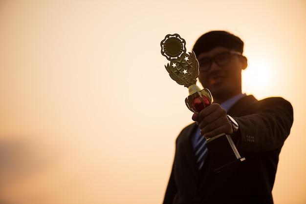 Homme d'affaires montrant le trophée d'or