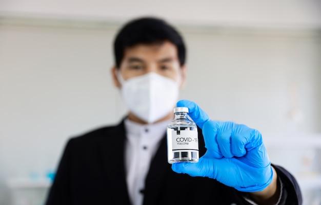 Homme d'affaires montrant le vaccin covid-19 en main