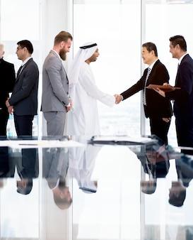 Homme d'affaires moyen-oriental ayant une poignée de main avec un homme d'affaires asiatique