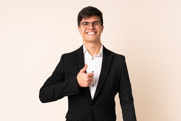 Homme affaires, sur, mur beige, donner, a, pouces haut, geste
