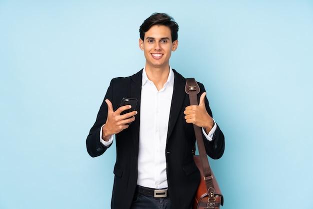 Homme affaires, sur, mur bleu, donner, a, pouces haut, geste