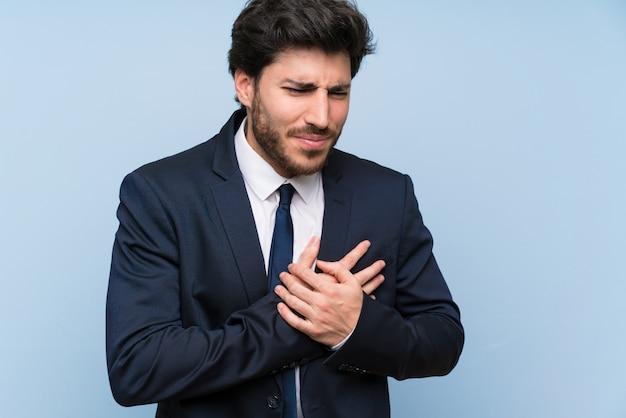 Homme d'affaires sur un mur bleu isolé ayant une douleur au coeur