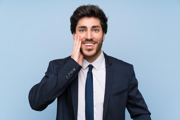 Homme d'affaires sur un mur bleu isolé avec une expression faciale surprise et choquée