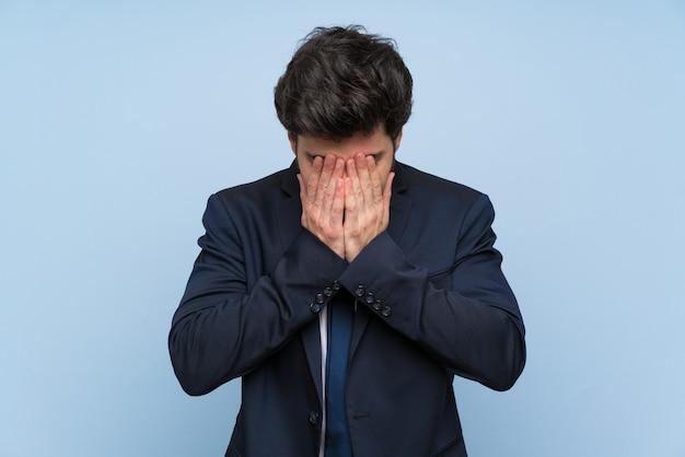 Homme d'affaires sur un mur bleu isolé avec une expression fatiguée et malade