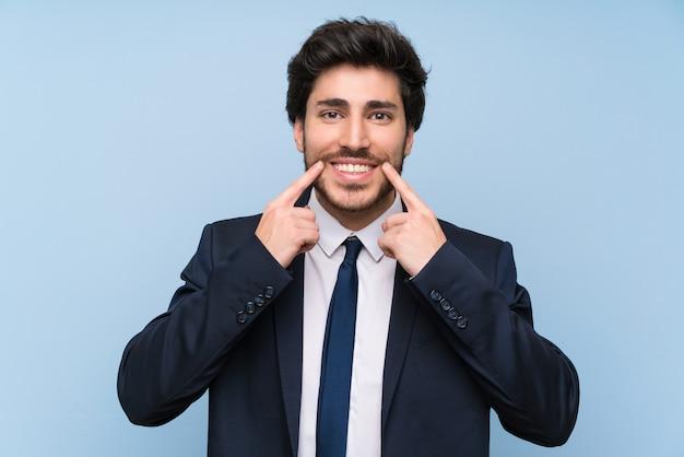 Homme d'affaires sur un mur bleu isolé, souriant avec une expression heureuse et agréable