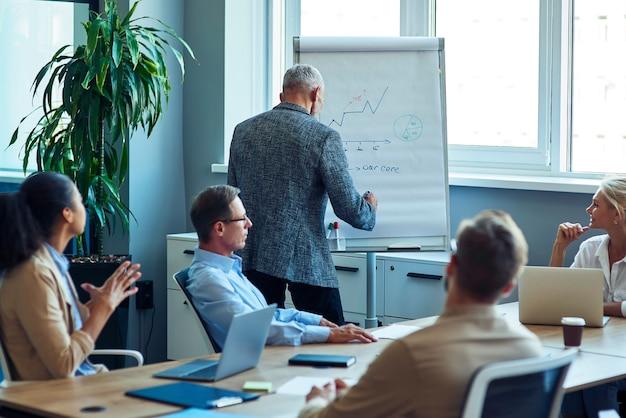 Homme d'affaires mûr écrivant quelque chose sur le tableau de conférence tout en ayant une réunion avec le multiracial