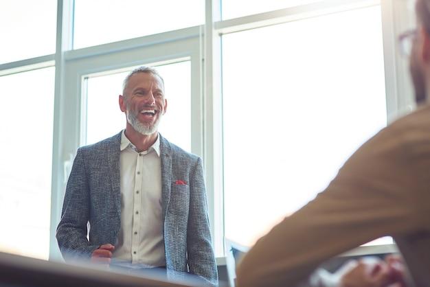 Homme d'affaires mûr gai discutant de quelque chose avec son jeune collègue masculin et souriant tout en