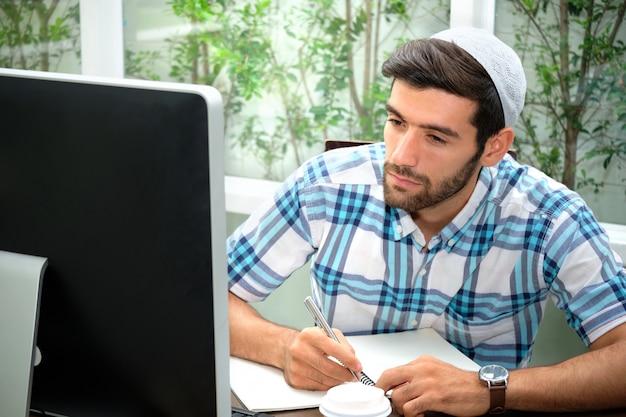 Un homme d'affaires musulman porte une casquette de taqiyah, sa main tenant un stylo pour rédiger des horaires de travail tout en regardant sur l'écran de l'ordinateur.