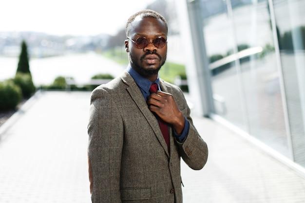 Homme d'affaires noir afro-américain élégant en poses de lunettes de soleil rondes