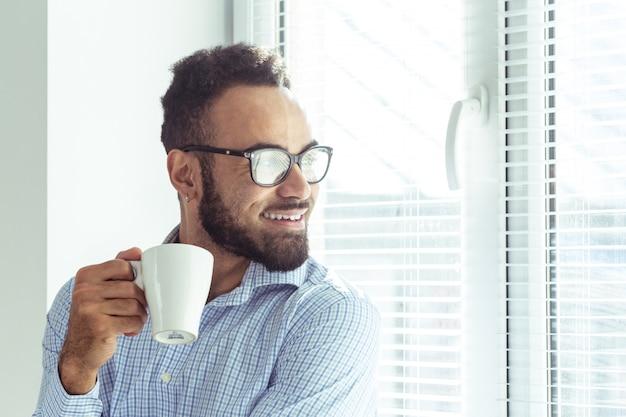 Homme d'affaires noir détendu au bureau, boire du café