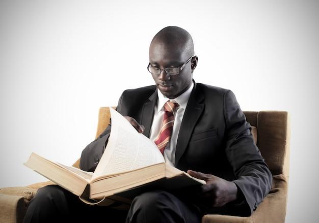 Homme d'affaires noir lisant un gros livre