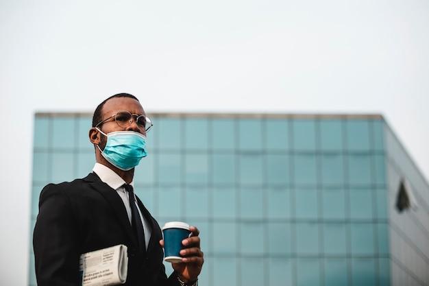 Homme d'affaires noir avec un masque de protection tient le journal et le café. grand fond de bâtiment