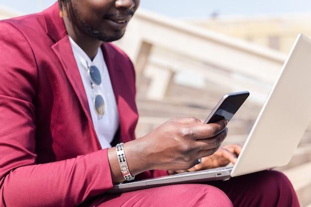 Homme d'affaires noir méconnaissable utilisant un smartphone et un ordinateur portable, technologie et concept de travail à distance, espace de copie pour le texte