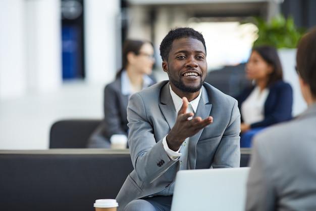 Homme d'affaires noir rencontre avec partenaire dans le hall