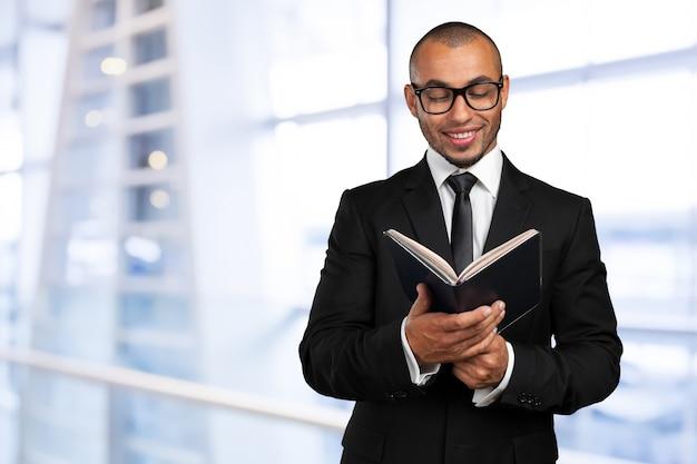 Homme d'affaires noir tenant un livre