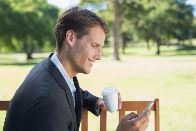 Homme d'affaires occasionnel textos sur téléphone sur un banc de parc