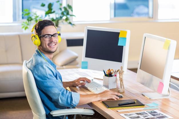 Homme d'affaires occasionnel travaillant à son bureau et écouter de la musique