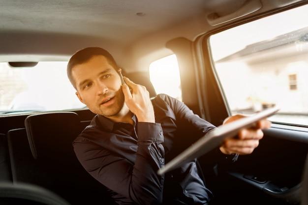 Homme d'affaires occupé dans un taxi. concept multitâche. le passager monte sur le siège arrière et travaille simultanément. parle sur un smartphone et utilise une tablette pc et communique avec le conducteur