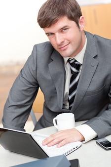 Homme d'affaires occupé avec un ordinateur portable, un téléphone portable et une tasse assis à