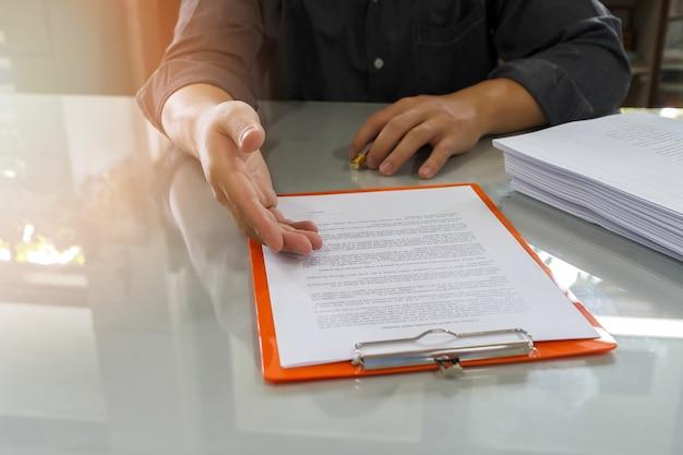 Homme d'affaires offrant un contrat de papier à son partenaire d'affaires pour le contrat de signe