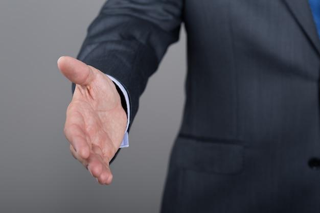 Homme d'affaires offrant sa main pour la poignée de main. geste de bienvenue ou de félicitations. réunion d'affaires et réussite