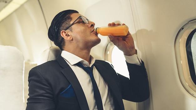 Homme d'affaires ont du jus d'orange servi par une hôtesse de l'air en avion