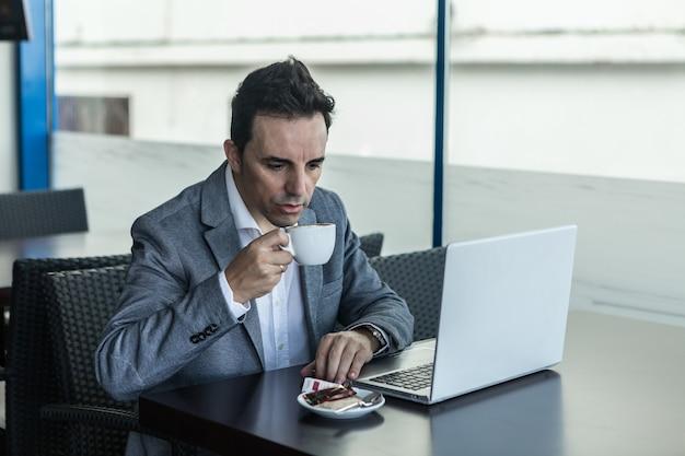 Homme affaires, à, ordinateur portable, boire café, dans, café