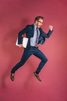 Homme d'affaires avec ordinateur sautant