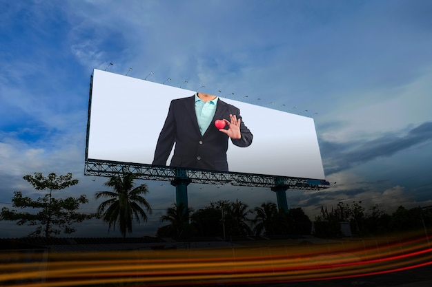 Homme d'affaires sur panneau publicitaire blanc sur ciel bleu.