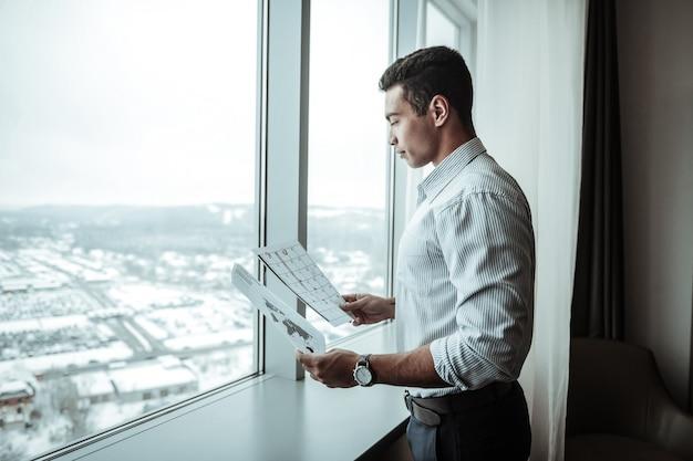 Homme d'affaires en pantalon. homme affaires, porter, pantalon foncé, et, chemise rayée, debout, près, fenêtre