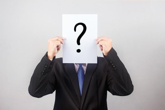 Homme d'affaires avec le papier de la question sur fond gris