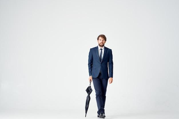 Homme d'affaires avec un parapluie et dans un costume classique en pleine croissance sur un fond clair