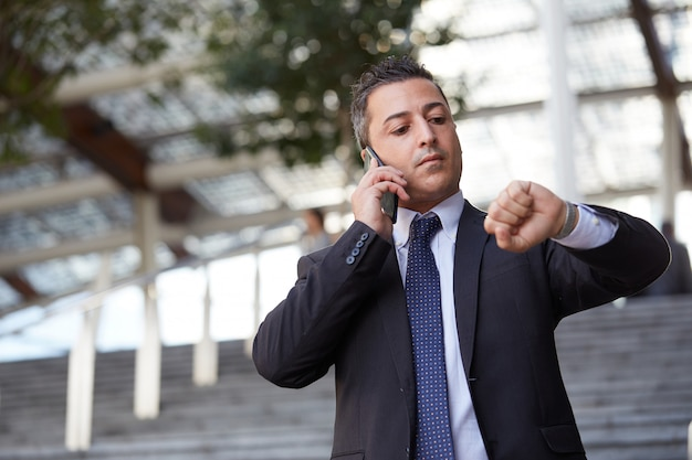 Homme d'affaires parlant au mobile en milieu urbain