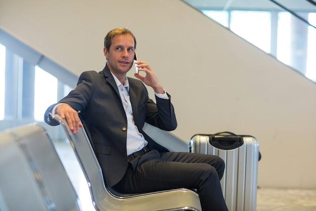 Homme d'affaires parlant au téléphone mobile dans la zone d'attente