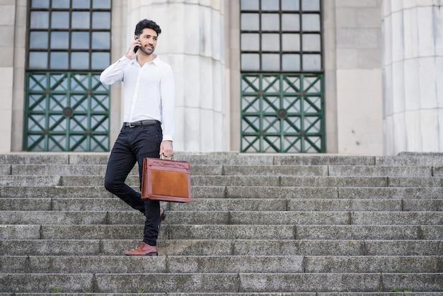 Homme d'affaires parlant au téléphone en se tenant debout dans les escaliers à l'extérieur. concept d'entreprise.