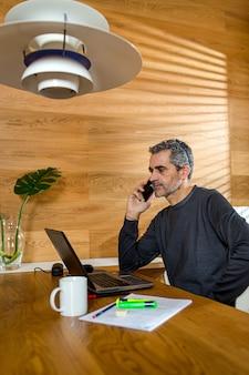 Homme d'affaires parlant au téléphone et travaillant sur son ordinateur portable dans son salon