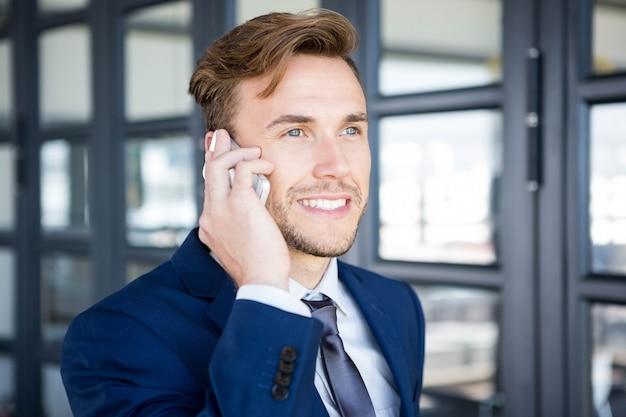 Homme d'affaires parlant sur smartphone au bureau