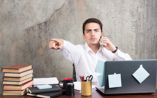 Homme d'affaires parlant avec téléphone et pointant vers l'avant au bureau.