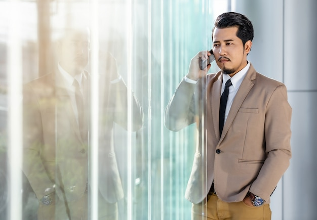 Homme d'affaires parlant avec un téléphone portable au bureau