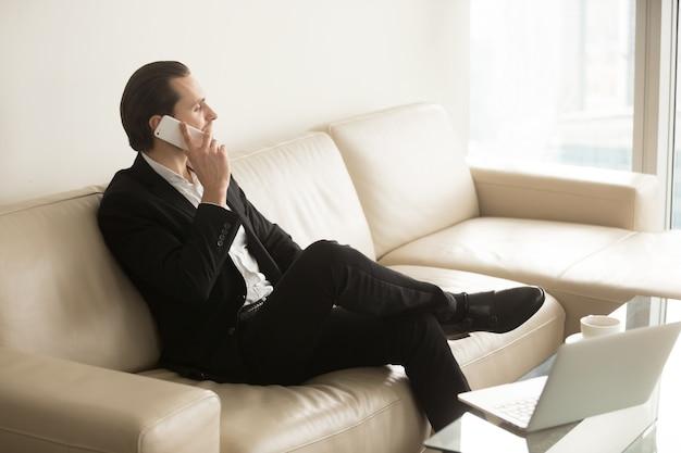 Homme d'affaires parle au téléphone tout en restant assis sur le canapé.