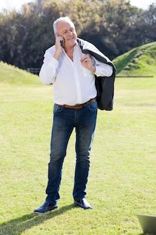Homme d'affaires à parler au téléphone et tenant sa veste
