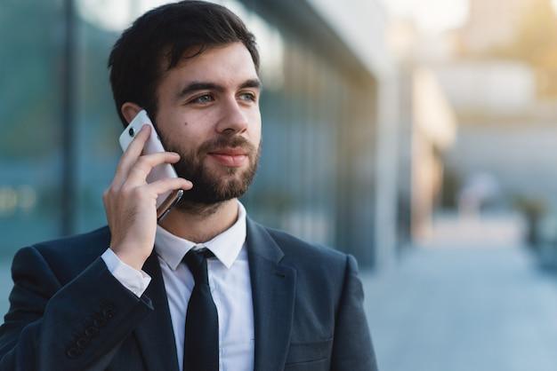Homme affaires, parler, sur, smartphone, contre, les, bâtiment entreprise, dehors