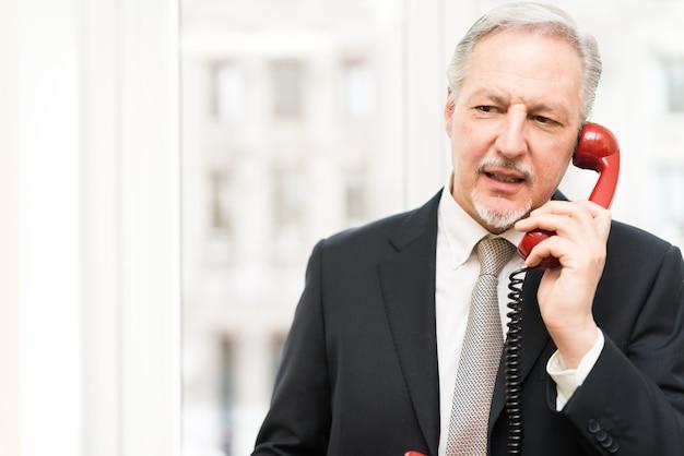 Homme d'affaires, parler sur un téléphone vintage dans son bureau