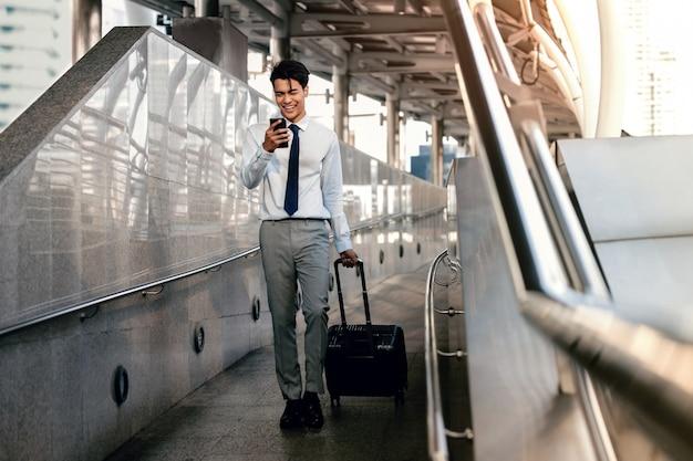 Homme d'affaires de passager souriant à l'aide de téléphone portable en marchant avec une valise dans l'aéroport ou la gare de transports en commun. mode de vie des gens modernes. toute la longueur