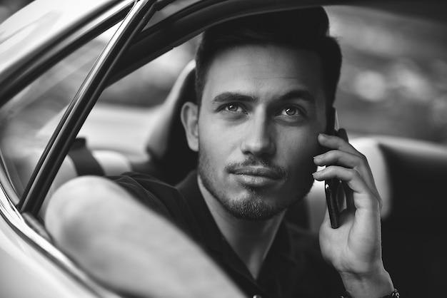 Un homme d'affaires passager utilise un smartphone sur le siège arrière de la voiture.