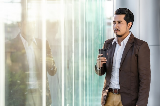 Homme d'affaires pensant et tenant une tasse de café au bureau