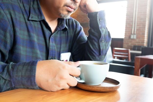 Un homme d'affaires pense sérieusement à une transaction alors qu'il boit du café chaud