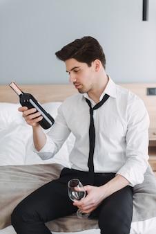 Homme d'affaires de pensée brune portant des vêtements formels tenant une bouteille de vin et de verre alors qu'il était assis sur le lit dans l'appartement de l'hôtel